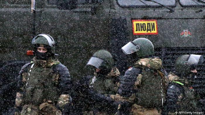 Белорусские силовики у автозака с надписью Люди