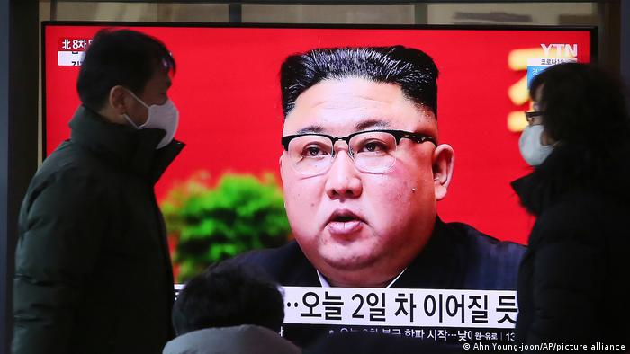People walk by a TV screen showing North Korean leader Kim Jong Un during a ruling party congress