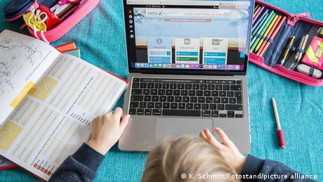 Ein Kind sitzt an einem Tisch, auf dem ein aufgeklappter Laptop, Übungshefte und ein Mäppchen mit Stiften liegen.