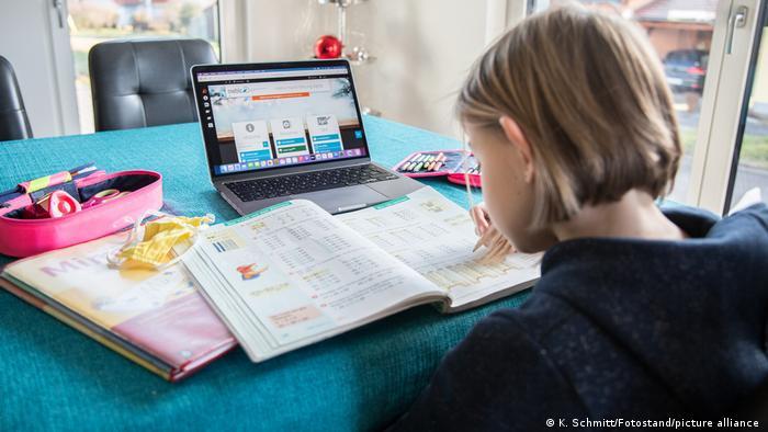 Criança estuda sentada em frente a um laptop, utensílios escolares, um livro aberto e uma máscara de proteção facial sobre a mesa.