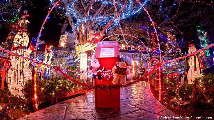 Weihnachtsbeleuchtung in Park. Lichterketten um Bäume, bleuchtete Schneemänner