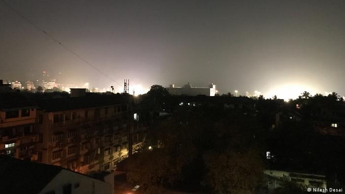 Häusersilluette mit leuchtenden Lichtkegeln, die den Himmel aufhellen