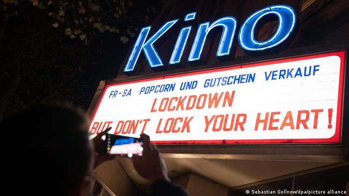 Cinema neon sign with the inscription: Lockdown but don't lock your heart!