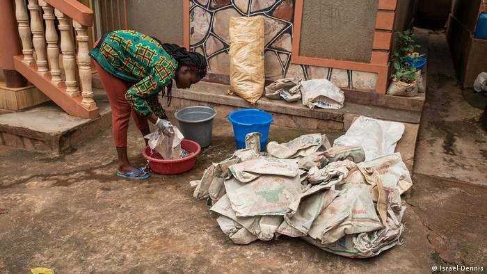 A woman washes plastic wrap in a vat in Mpigi, Uganda