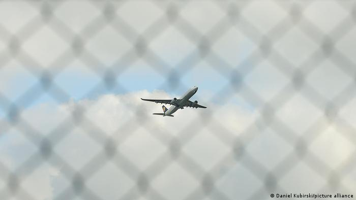 An airplane takes off behind a chain-link fence
