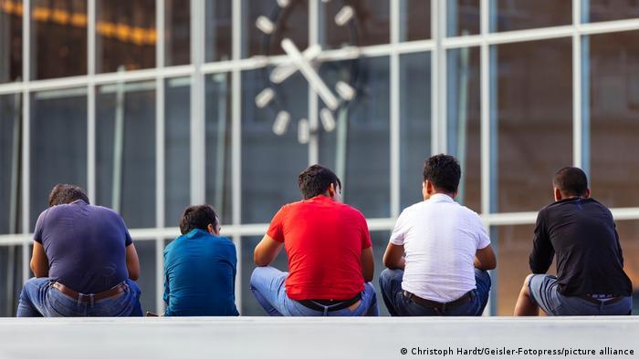 Muškarci sjede ispred kolodvora