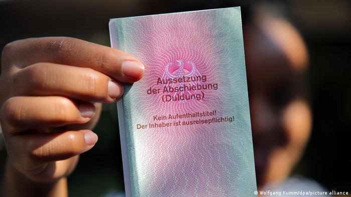 A refugee holds an identity card for refugees in her hand with the title: Suspension of deportation