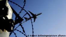 Ein Flugzeug fliegt am 02.11.2015 am Flughafen Berlin-Tegel hinter Stacheldraht (Symbolbild zum Thema Abschiebung). Foto: picture alliance / Robert Schlesinger