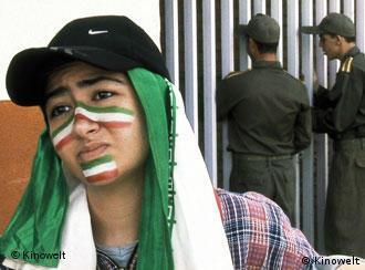 Iranische Frau mit Bemalung und Kopftuch in Landesfarben - daneben zwei Polizisten, die durch ein Gitter Fußball schauen - Szene aus Offside