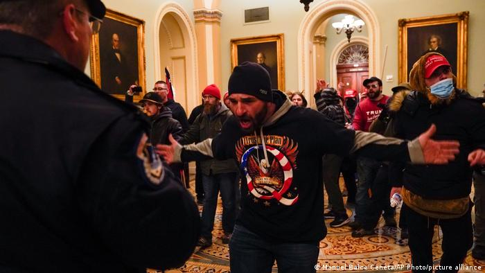 Protesters gesture to US Capitol police in the hallway outside the Senate chamber