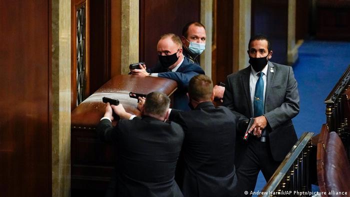 Agentes de seguridad desenfundaron sus armas para proteger a los legisladores.