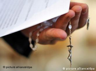 A priests's hand close up, holding a rosary and a church statement on abuse cases.