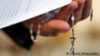 priest with handcuffs covering his face and holding a cross