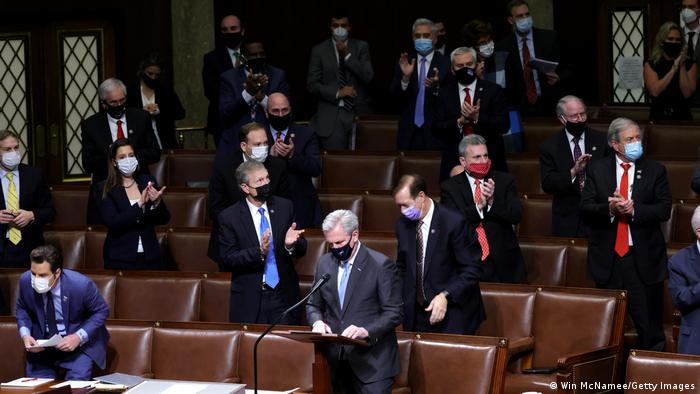 House Minority Leader Kevin McCarthy (R-CA) and members of congress applaud in the House Chamber during a reconvening of a joint session of Congress
