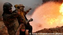 Iraqi fire fighters try to extinguish oil wells set on fire near Mosul by the extremist IS group as it fled the area