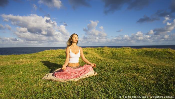 A woman sitting cross-legged on the grass