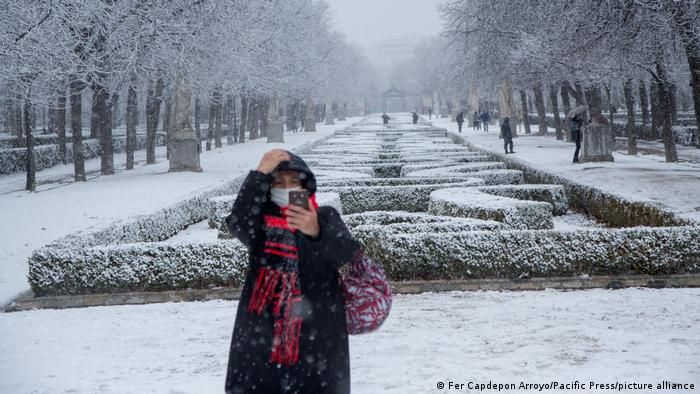 A woman takes a selfie in a snowy Spanish park in Madrid