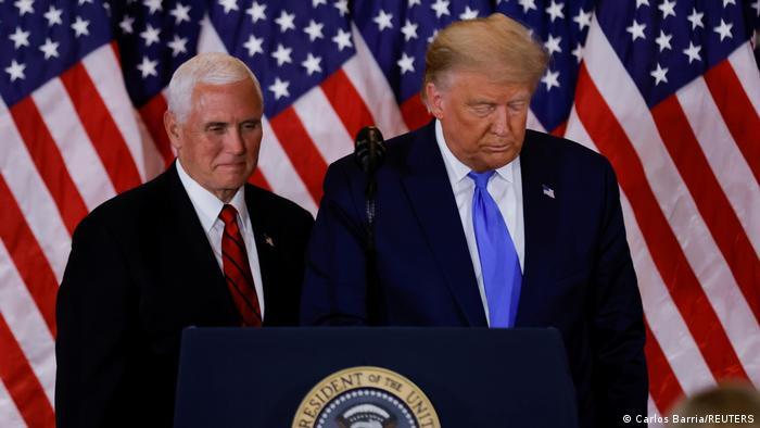 Trump e Mike Pence em um púpito, Trump olha para baixo e Pence esboça um leve sorriso. Ao fundo há quatro bandeiras americanas.