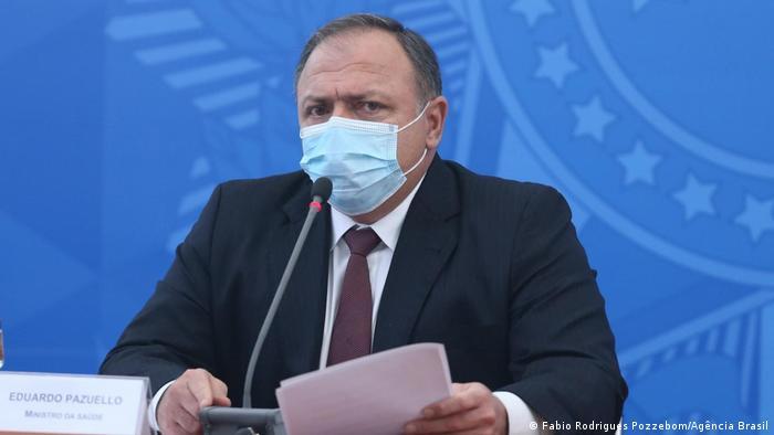 Pazuello, de terno e gravata escuros, fala em um microfone. Ele usa máscara, está sentado e segura alguns papéis.