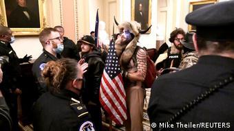 Agentes tentam barrar homem vestido com um capacete com chifres e pele de animal durante invasão do Capitólio