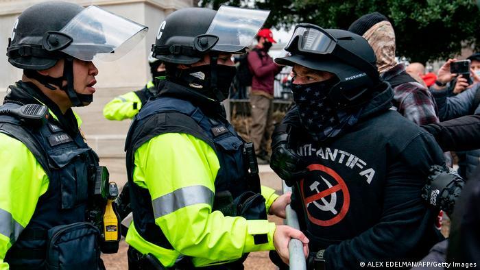 Polizisten und ein Mitglied der Proud Boys stehen sich gegenüber