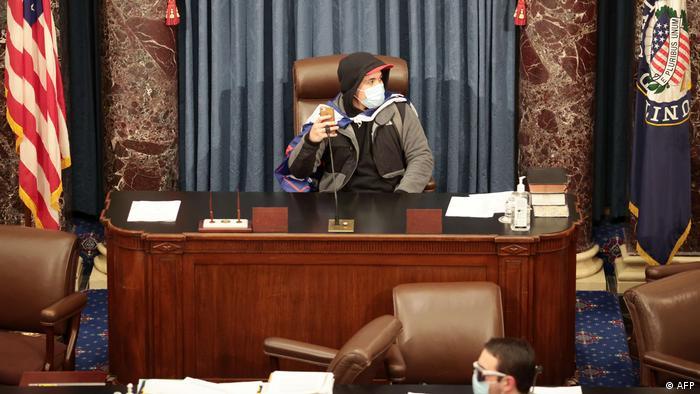 Сторонник Трампа сидит в кресле сенатора во время захвата Конгресса США 6 января 2021 года