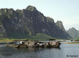 Boote auf einem See, im Hintergrund ein großer Felsen