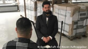 Der Auftraggeber und Hauptdarsteller des Comics Temple of Refuge Sartep Namiq im Interview vor einer Palette gedruckter Exemplare