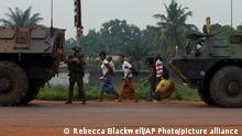 Residents carry their belongings as they flee past French armored personnel carries, in the Miskine district of Bangui, Central African Republic, Thursday, Dec. 26, 2013. The spokesman for an African Union peacekeeping force says six Chadian peacekeepers were killed and 15 were wounded, after being attacked Wednesday.(AP Photo/Rebecca Blackwell)