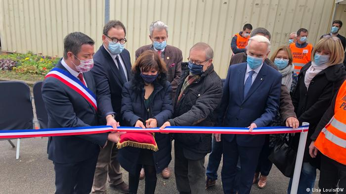 Group of people cutting a tricolored band to open the vaccination center in Poissy