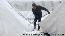 A migrant clears snow from tents at the Lipa camp in Bosnia.