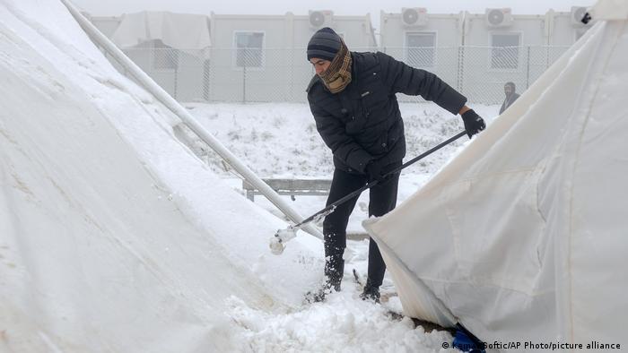 Migrant oko izgorjelog kampa Lipa čisti snijeg