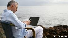 Man on a chair at the beach with his laptop