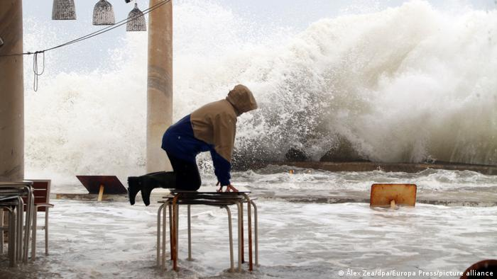 A man kneeling on a stack of tables to escape the water as a large wave approaches