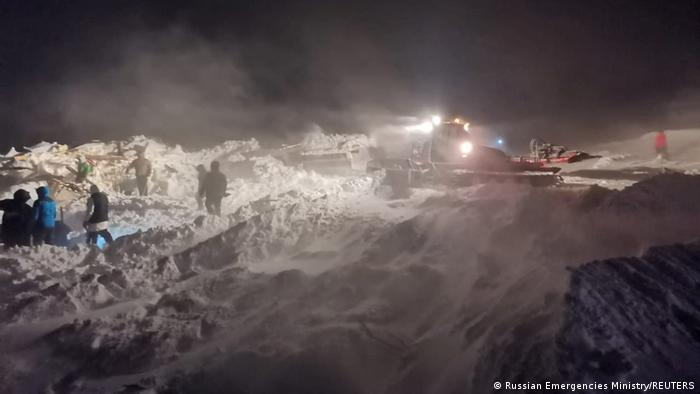Rescuers and volunteers take part in a search operation after an avalanche hit a ski resort