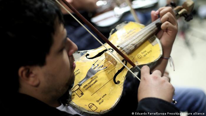 Hombre tocando un violín fabricado con material reciclado.