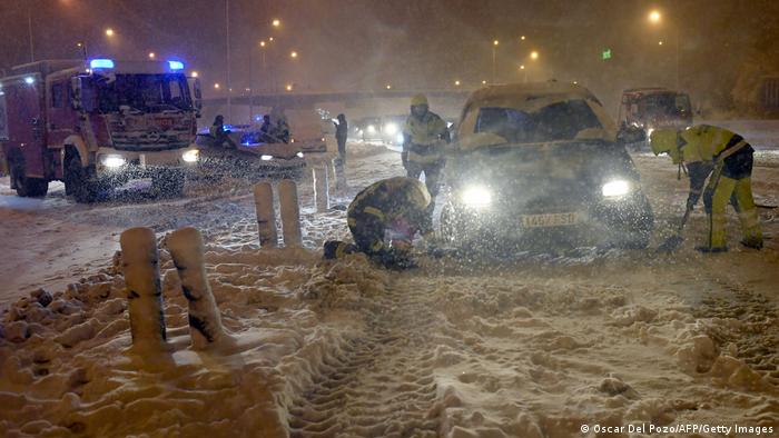 Spanish firefighters help dig cars out of the snow in the capital Madrid