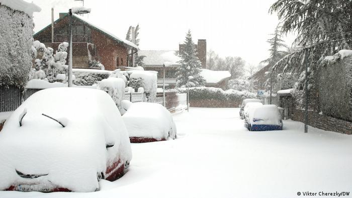 Carros e rua sob neve em Madri