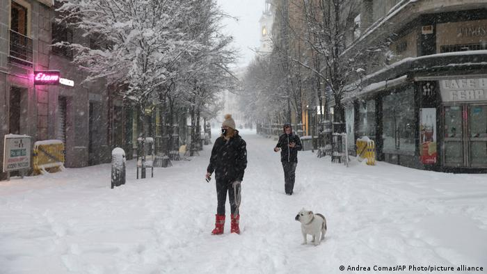 Two people walking their dog through snow-covered streets in Madrid.