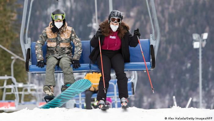 Skiers with protective face masks leave a chairlift in Austria