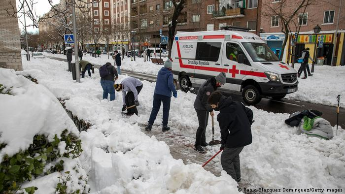 People clear snow on roadside as ambulance passes
