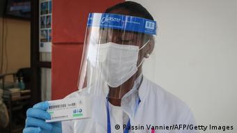 Человек в защитной маске держит в руках упаковку с китайской вакциной от коронавируса