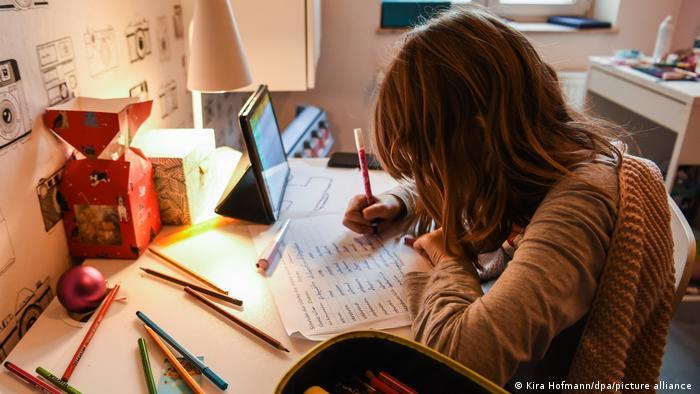 Урок онлайн: ребенок сидит за столом перед включенным планшетом