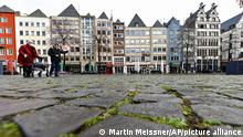 People cross an empty square in downtown in Cologne Germany