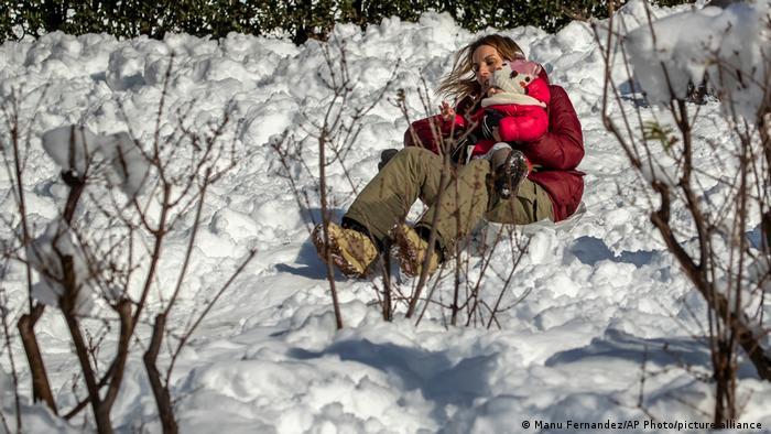 Tormenta de nieve en España: una mujer se desliza con su bebé por la nieve.