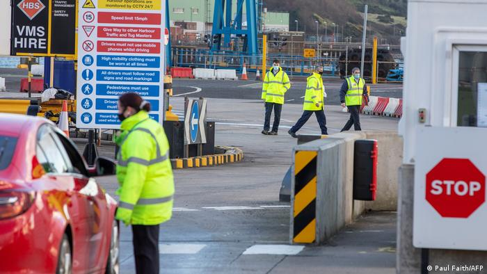 An official checks a motorist as truckers disembark a ferry at the Port of Larne, Northern Ireland