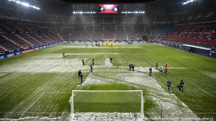 Workers clear snow from the pitch before the start of a Spanish La Liga soccer match between Osasuna and Real Madrid at El Sadar stadium in Pamplona, Spain