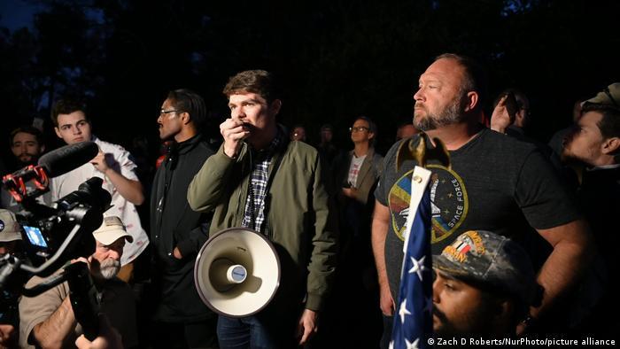 Nick Fuentes mit Megaphon bei einer nächtlichen Kundgebung der Stop the Steal Bewegung in Georgia inmitten weiterer Demonstranten