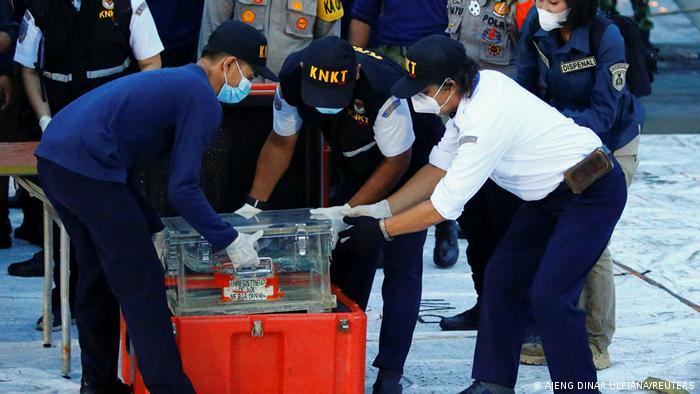 National Transportation Safety Committee (KNKT) officials hold a part of the retrieved black box of Sriwijaya Air flight SJ 182