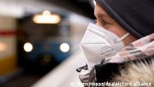 A woman wearing an FFP2 mask waits for a subway train in Germany